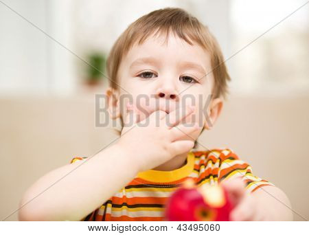 Little boy is eating red apple