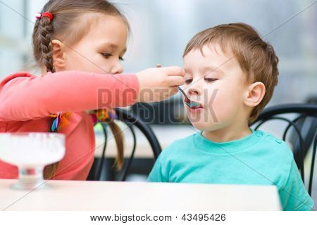 Girl is feeding his little brother with ice-cream in parlor