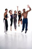 pic of young adult  - Group of multiracial young adults jumping with joy in fitness wear. All logos removed.