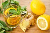 stock photo of mug shot  - ginger in a cup of tea with lemon and mint - JPG