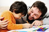 stock photo of daddy  - Father and little boy of fivr years having fun painting at home - JPG