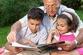 foto of girl reading book  - Grandfather and kids reading book outdoors  - JPG