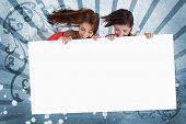picture of cursive  - Smiling girls looking down at white copy space screen on blue art deco style background - JPG