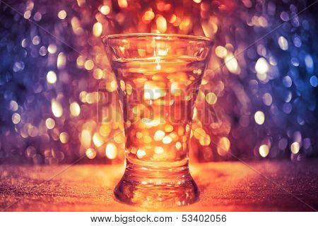 shot glass of vodka on shiny festive background