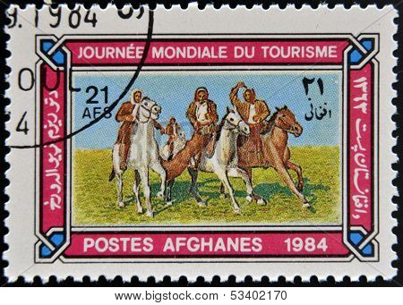 AFGHANISTAN - CIRCA 1984: A stamp printed in Afghanistan shows Horsemen playing Tourism buzkashi