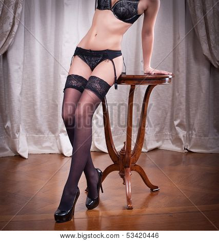 Sexy beautiful body shot of young woman wearing black lingerie and stockings.Long legs in black