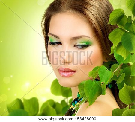 Beautiful Girl with Green Leaves. Fresh Skin. Skincare concept. Nature. Spring Beauty Woman outdoors. Perfect Face skin. Organic cosmetics