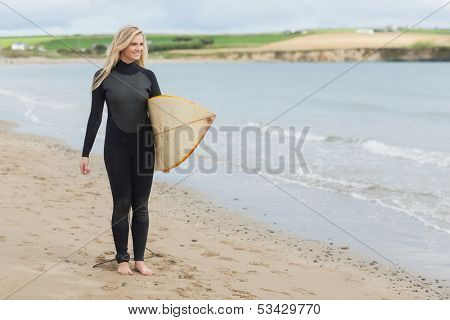 Full length of a beautiful young woman in wet suit holding surfboard at the beach