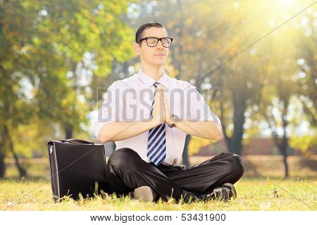 Young businessperson with tie doing yoga exercise seated on a green grass in a park