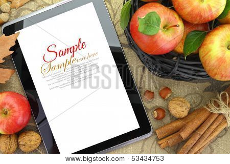 Autumn background basket with apples and tablet