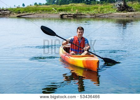 Man With Safety Vest Kayaking Alone On A Calm River