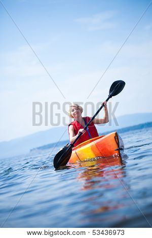 Woman With Safety Vest Kayaking Alone On A Calm Sea