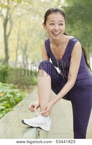 Young woman tying her shoe