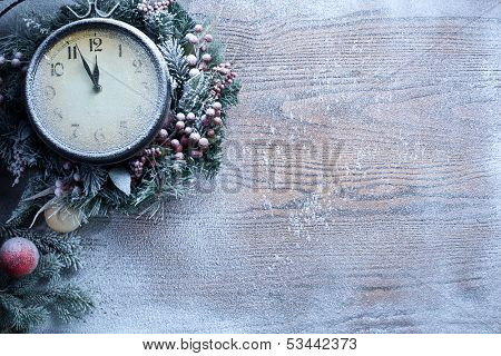 Christmas clock over snow wooden background. Five to twelve.