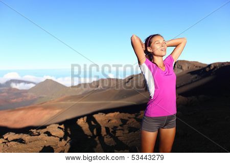 Runner Athlete woman relaxing after running. Fitness girl resting after training outside in beautiful nature landscape. Fit sport fitness model outdoors at sunset. Multi-ethnic Asian Caucasian female.
