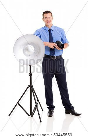 happy male photographer in studio standing next to beauty dish