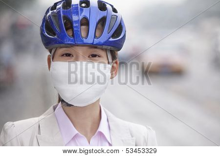 Young business woman wearing bicycle helmet and face mask