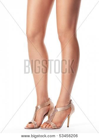 Closeup of young woman legs wearing high heel sandals isolated on white background
