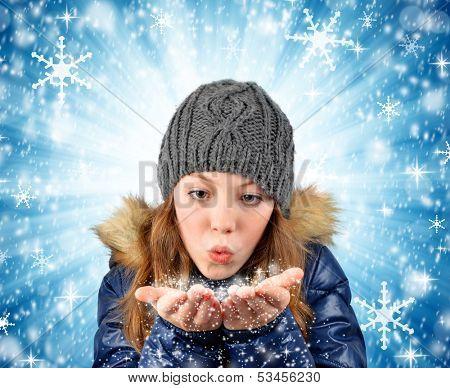 Winter portrait girl blowing snow