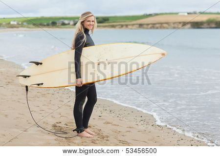 Full length portrait of a beautiful young woman in wet suit holding surfboard at the beach