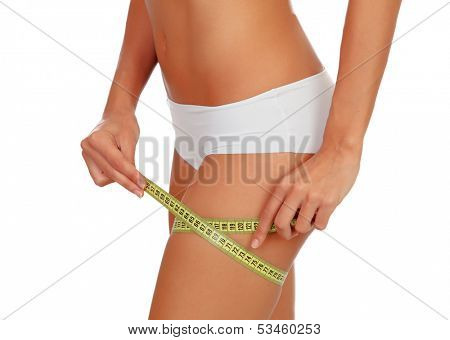 Girl in black underwear with a tape measure around her thigh isolated