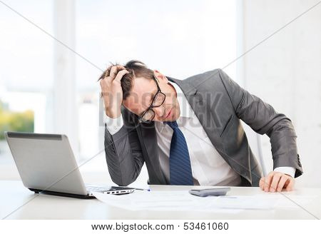business, office, school and education concept - stressed businessman with laptop computer, papers and calculator