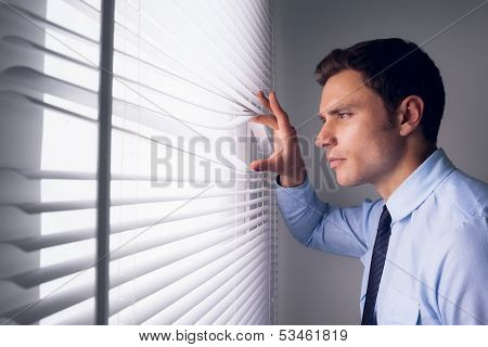 Side view of a young businessman peeking through blinds in office