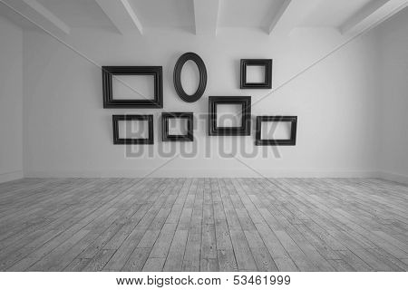 Big room with several frames at wall and floorboards