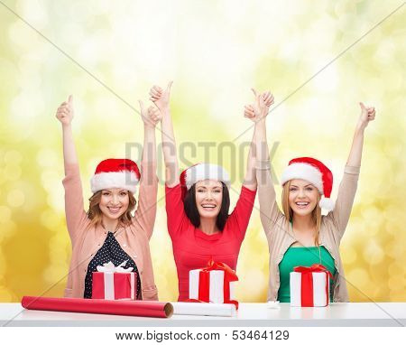 christmas, x-mas, winter, happiness concept - three smiling women in santa helper hats with gift boxes