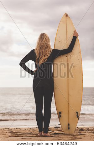 Full length rear view of a young blond in wet suit with surfboard at the beach
