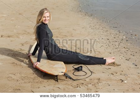 Side view portrait of a beautiful blond in wet suit with surfboard at the beach