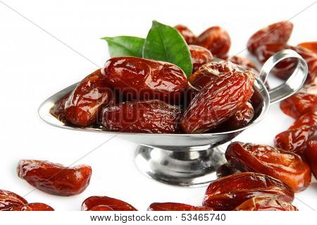 Dried dates in metal dish isolated on white