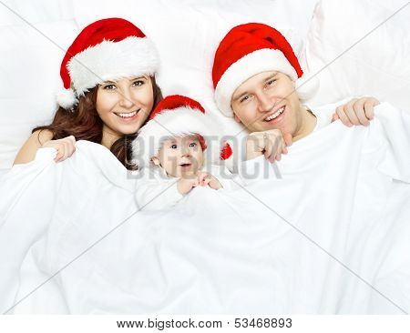Christmas Family And Baby In Santa Claus Hat Lying In White Background