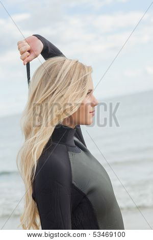 Side view of a young blond in wet suit standing at the beach