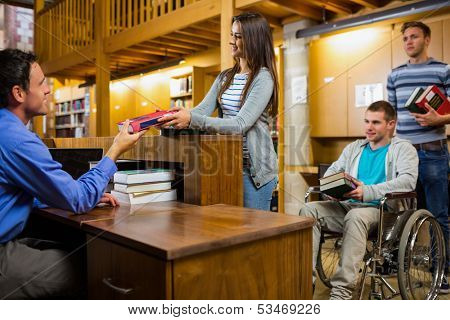 Students with handicapped man in row at the counter in college library
