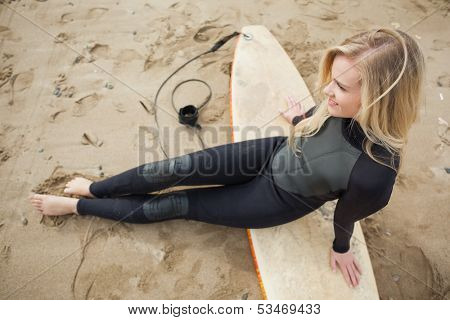 Overhead view of a smiling beautiful blond in wet suit with surfboard at the beach