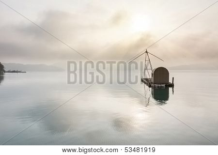 Landscape of famous Sun Moon Lake in the morning with a boat and mist in Taiwan, Asia.