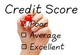 stock photo of performance evaluation  - Hand putting check mark with red marker on poor credit score evaluation form - JPG