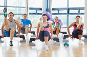 pic of physical exercise  - Full length of instructor with fitness class performing step aerobics exercise in gym - JPG