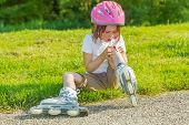 stock photo of scrape  - Preschool roller skate beginner looking at her bleeding knee - JPG
