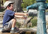picture of water shortage  - Child filling water bottle from a hydrant fountain - JPG