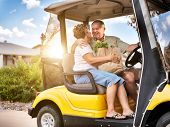 image of golf bag  - happy elderly couple coming home with groceries on golf cart - JPG