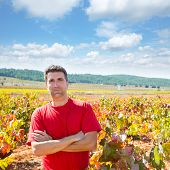 Harvester winemaker farmer proud of his vineyard in autumn golden red leaves at Mediterranean