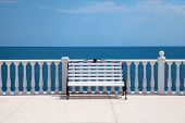 stock photo of bannister  - Summer view with classic white balustrade bench and empty terrace overlooking the sea  - JPG
