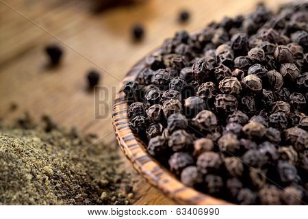 Black Pepper on wooden table. Soft focus