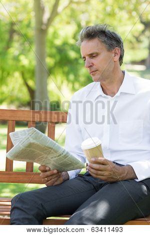 Businessman with disposable cup reading newspaper in the park