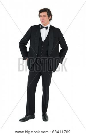 Full length of handsome groom looking away over white background