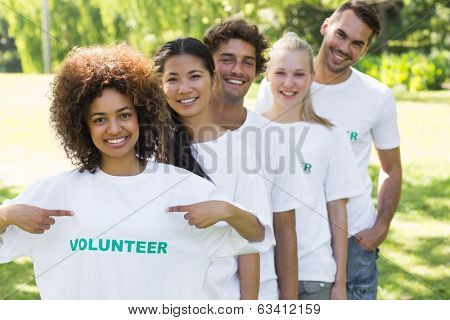 Portrait of environmentalist showing volunteer tshirt with friends standing in line behind