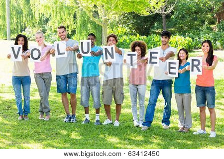Full length of friends holding placards spelling volunteer on campus