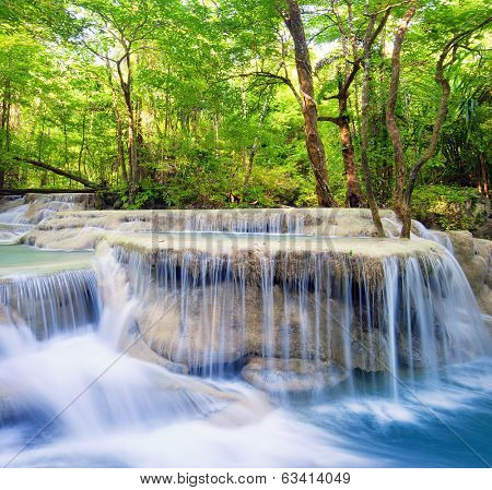 Waterfall landscape background. Beautiful nature outdoor photography. Thailand green rain forest jungle with trees and bushes, fresh clean and cool water river flows through stones cascades and roots